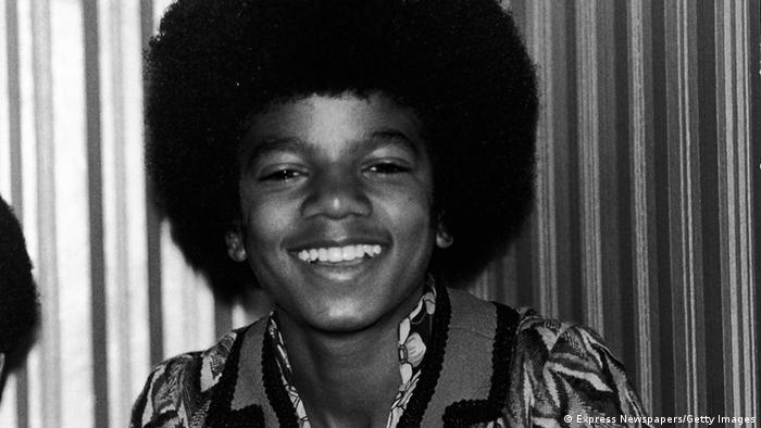 A young Michael Jackson smiles into the camera