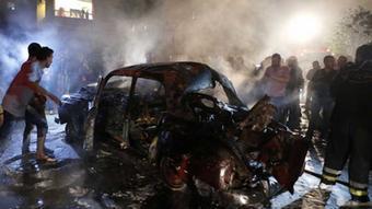 Menschen stehen neben einem ausgebrannten Autowrack @REUTERS/Mohamed Azakir