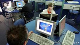 Menschen vor Bildschirmen in Internetcafe (Quelle: AP)