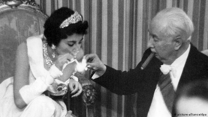 German President Theodor Heuss lights a cigarette for Iranian Queen Soraya