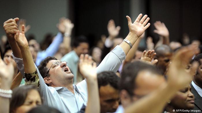 Fiéis levantam os braços para o alto durante culto da igreja Assembleia de Deus em Goiânia