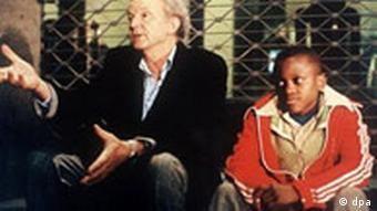 Mann und Junge vor Gitter sitzend (die Schauspieler Michael Gwisdek und Ricardo Valentim)