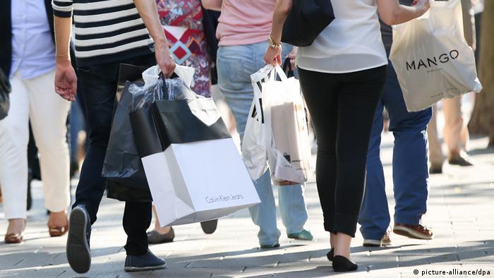 Menschen laufen mit verschiedenen Arten von Tüten in der Hand durch eine Einkaufspassage