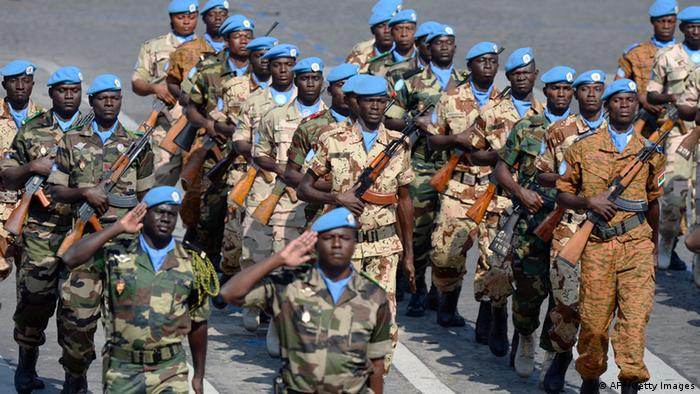 A group of African soldiers wearing blue UN helmets on parade