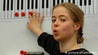 Eine Sängerin steht vor einer Klaviertastatur, auf der rote Punkte Töne markieren
