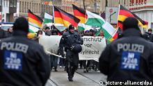 NPD-Mitglieder demonstrieren am 07.12.2013 gegen eine Asylbwerber-Notunterkunft in Leipzig (Sachsen). Mehrere hundert Gegendemonstranten haben den Aufmarsch von rund 100 Rechtsradikalen vor einer Asylbewerberunterkunft später verhindert. Foto: Jan Woitas/dpa