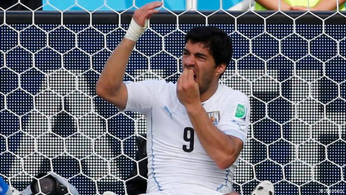 Luis Suarez holds his teeth during the 2014 World Cup Group D soccer match between Uruguay and Italy at the Dunas arena in Natal in this June 24, 2014 file photograph. Uruguay striker Suarez was banned for nine matches by FIFA on June 26, 2014 after being found guilty of biting Italian defender Chiellini on June 24, 2014. Suarez was also banned from any football-related activity for four months and fined 100,000 Swiss francs ($111,000). REUTERS/Yves Herman/Files