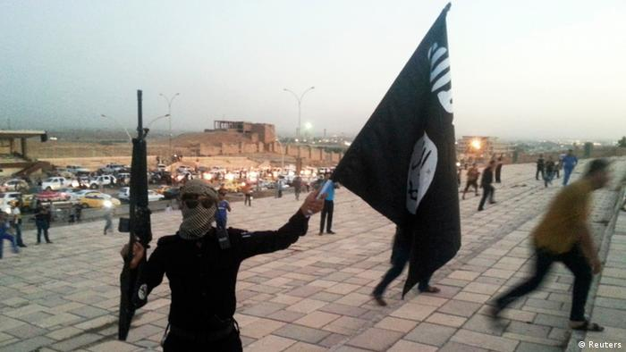 An ISIS fighter holds up a weapon and a flag