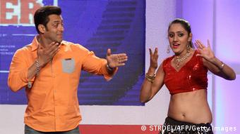 Bollywood actor Salman Khan (L) dances with a participant during the launch of a television event in Mumbai on late March 23, 2014 (Photo: STRDEL/AFP/Getty Images)