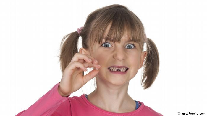 A girl with a milk tooth in her hand (luna/Fotolia.com)