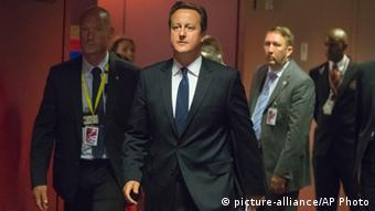 David Cameron, center, walks to a media conference after an EU summit in Brussels on June 27, 2014