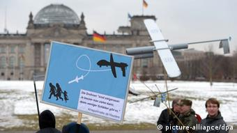 Protesters hold up anti-drone posters in front of the Bundestag building in Berlin. (Photo: Rainer Jensen/dpa)