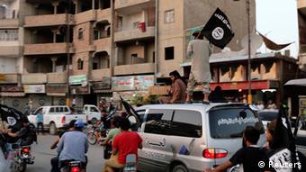 Raia wakipeperusha bendera za IS katika mji wa Raqqa nchini Syria.