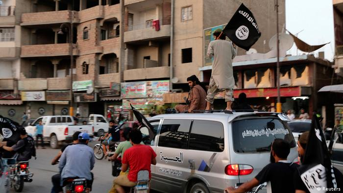 Members loyal to the Islamic State in Iraq and Syria wave ISIS flags as they drive around Raqqa. REUTERS/Stringer