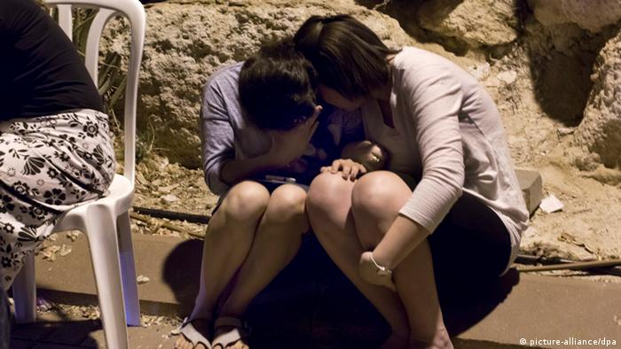 Girls crying on a sidewalk. (Photo: EPA/JIM HOLLANDER)