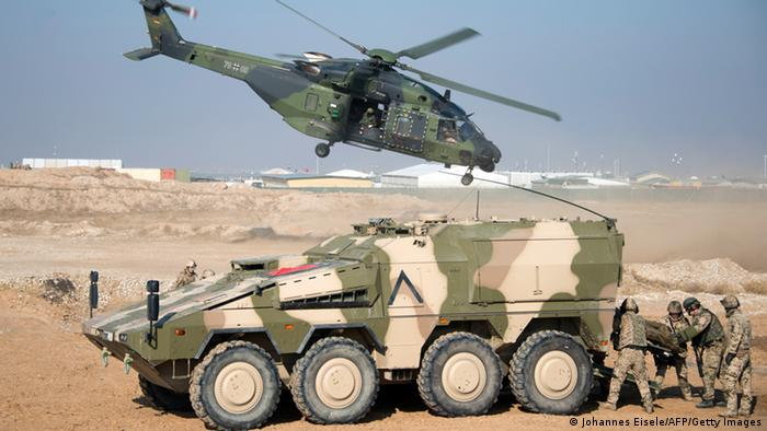 A German Bundeswehr NH90 helicopter flies past a Boxer armoured fighting vehicle .