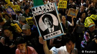 Protesters holding placards shout slogans at a rally against Japan's Prime Minister Shinzo Abe's push to expand Japan's military role in front of Abe's official residence in Tokyo June 30, 2014.