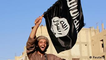 A militant Islamist fighter uses a mobile to film his fellow fighters taking part in a military parade along the streets of Syria's northern Raqqa province June 30, 2014. The fighters held the parade to celebrate their declaration of an Islamic caliphate after the group captured territory in neighbouring Iraq, a monitoring service said. The Islamic State, an al Qaeda offshoot previously known as Islamic State in Iraq and the Levant (ISIL), posted pictures online on Sunday of people waving black flags from cars and holding guns in the air, the SITE monitoring service said. Picture taken June 30, 2014. REUTERS/Stringer