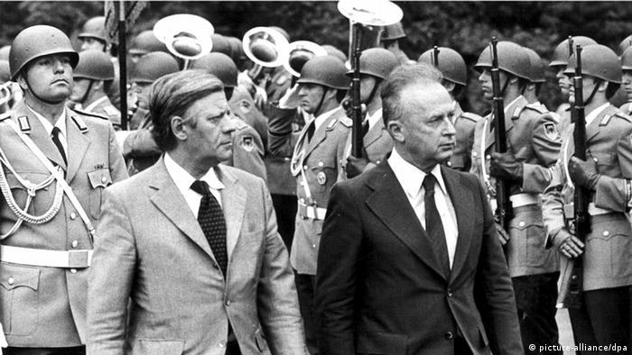 Foto em preto e branco com dois homens de paletó e gravata. Atrás, soldados perfilados