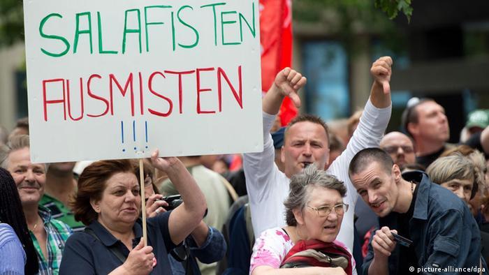 Gegendemonstrantin auf einer Kundgebung des radikalen Salafistenpredigers Pierre Vogel (Foto: Boris Roessler/dpa)