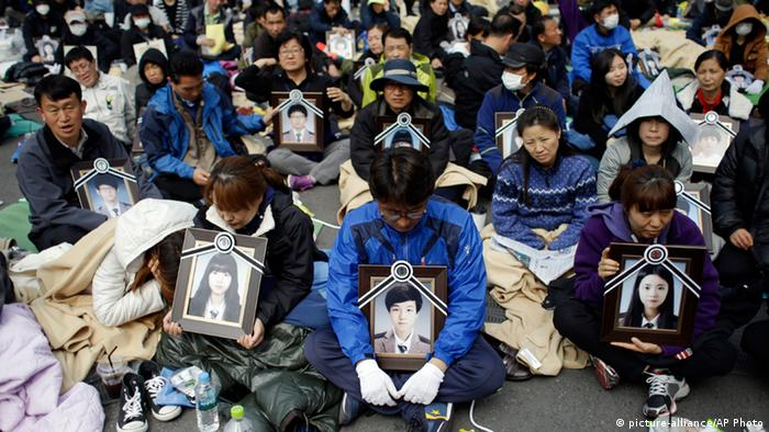 Family members holding the portraits of the victims of the sunken ferry Sewol, sit on a street near the presidential Blue House in Seoul, South Korea, Friday, May 9, 2014. Family members marched to the presidential Blue House in Seoul early Friday calling for a meeting with President Park Geun-hye but ended up sitting on streets near the presidential palace after police officers blocked them. Park's office said a senior presidential official plans to meet them later Friday. (AP Photo/Lee Jin-man)Südkorea Fährunglück Familienangehörige 09.05.2014 Seoul