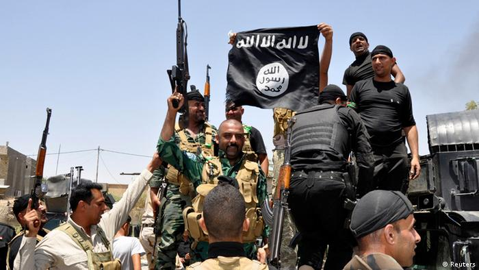 پرچم داعش در دست سربازان عراقی، نیروهای دولت مرکزی عراق در چندین جبهه سرگرم جنگ با نیروهای داعش و شورشیان سنی هستند