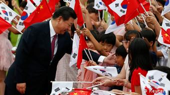 Chinese President Xi Jinping greets children waving Chinese and South Korean national flags during a welcoming ceremony at the presidential Blue House in Seoul July 3, 2014 (REUTERS/Kim Hong-Ji)