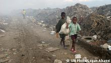 Children Scavenge for Valuables in Garbage Dump in Haiti. Members of the Chilean and Brazilian contingents of the United Nations Stabilization Mission in Haiti (MINUSTAH) conduct rehabilitation works and CIMIC (Civil-Military Cooperation) activities in Haiti. Many corners of Port-au-Prince are covered with mountains of garbage. Children carry plastics and metals for recycling scrounged from the smoldering garbage dump of Port-au-Prince through this road that is muddy and dusty. The construction of the new road is one of the CIMIC projects. 08 September 2009. Port-au-Prince, Haiti. Photo # 407767 . UN Photo/Logan Abassi