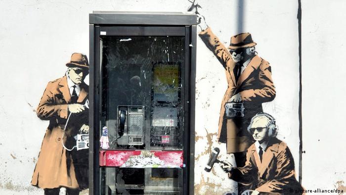 Grafitti in Cheltenham zeigt neben einer Telefonzelle drei abhörende Agenten. (Copyright: dpa) Vermutlich neues Banksy-Bild entdeckt