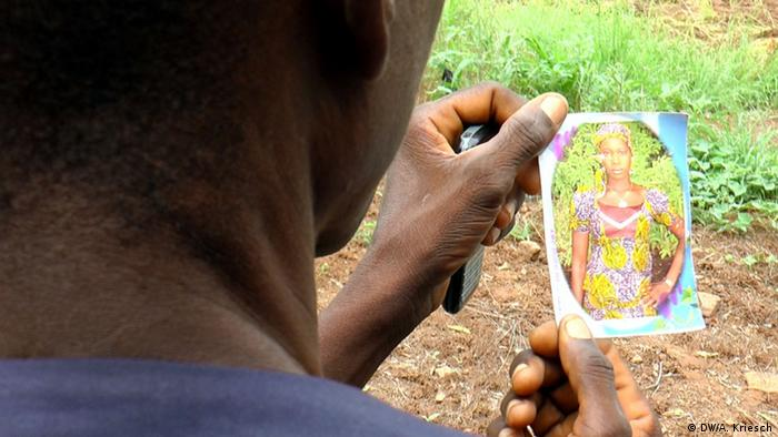 A man from Chibok looks at the picture of a girl.