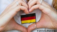 Eine Frau zeigt am 04.07.2014 in Berlin beim Public Viewing am Brandenburger Tor während dem WM-Viertelfinalspiels Deutschland - Frankreich ein Herz. Deutschland gewinnt am Ende mit 1:0 und steht im Halbfinale. Foto: Daniel Bockwoldt/dpa +++(c) dpa - Bildfunk+++