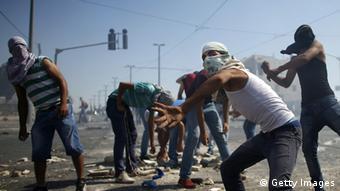 Wapalestina wakiwavurumishia mawe polisi wa Israel katika kitongoji cha Shuafat.