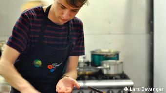 Koki sukarelawan Adam Nealon menyiapkan hidangan dari sampah makanan
