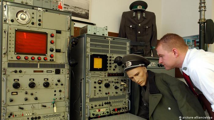 Ein Mann schaut in einem Museum auf eine alte Stasi-Abhöranlage, vor der eine Puppe eines Stasi-Offiziers steht (picture-alliance/dpa)