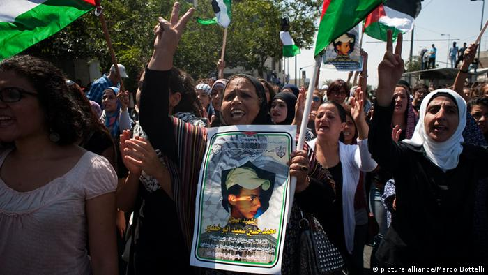 Palestinian women walk in a protest during the funeral of Mohammed Abu Khdeir on July 4, 2014