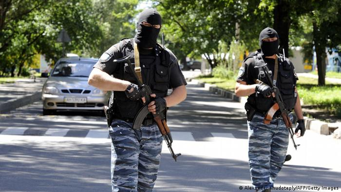Masked armed men wearing uniforms with the emblem of the Berkut, Ukraine's bisbanded elite riot police force, block the road near the police station in the centre of the eastern Ukrainian city of Donetsk on July 1, 2014. Ukrainian tanks and fighter bombers on July 1 launched a ferocious assault against pro-Russian separatist insurgents after rejecting European attempts to save a tenuous 10-day truce. AFP PHOTO/ ALEXANDER KHUDOTEPLY (Photo credit should read Alexander KHUDOTEPLY/AFP/Getty Images)