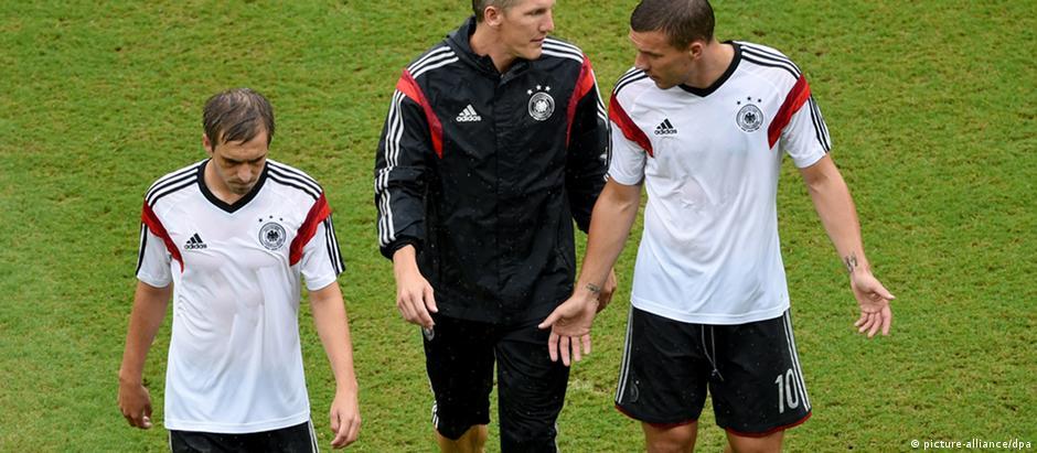 Os jogadores Philipp Lahm, Bastian Schweinsteiger e Lukas Podolski conversam na saída de um treino da seleção alemã