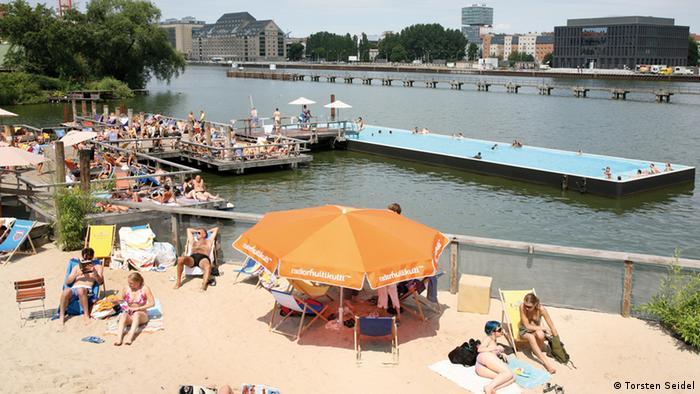 Badeschiff Berlin EINSCHRÄNKUNG Im Hintergrund schwimmt das Badeschiff auf der Spree. Vorne entspannen Menschen auf dem Sandstrand.