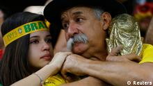 Brazilian fans react to their team's loss at the end of their 2014 World Cup semi-finals against Germany at the Mineirao stadium in Belo Horizonte July 8, 2014. REUTERS/Damir Sagolj (BRAZIL - Tags: SOCCER SPORT WORLD CUP)