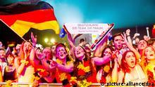 Deutschland-Fans jubeln am 08.07.2014 in Berlin beim Public Viewing am Brandenburger Tor nach dem WM-Halbfinalfußballspiel Deutschland - Brasilien im Bühnenlicht. Deutschland gewinnt mit 7:1. Foto: Daniel Bockwoldt/dpa