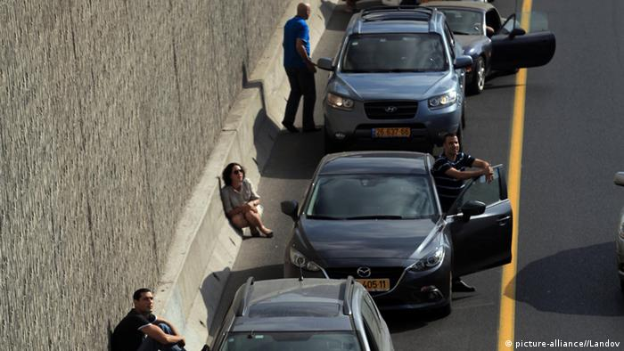 Israelis take cover near their cars on the central highway while sirens sound over Tel Aviv, Israel (Photo: Xinhua/JINI)