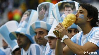 Argentinian fans hold a mock version of the World Cup trophy