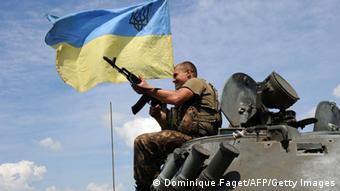 A tank with a man flying the Ukrainian flag (Photo: DOMINIQUE FAGET/AFP/Getty Images)