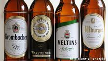 ILLUSTRATION - Bierflaschen der Brauereien Krombacher, Warsteiner, Veltins und Bitburger stehen am 13.01.2014 in Köln (Nordrhein-Westfalen) auf einem Tisch. Das Bundeskartellamt hat wegen verbotener Preisabsprachen bei Bier Bußgelder in Höhe von 106,5 Millionen Euro verhängt. Foto: Marius Becker/dpa