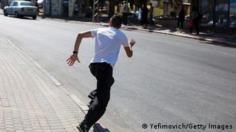 An Israeli takes cover from rocket fire in Sderot 10.7.2014