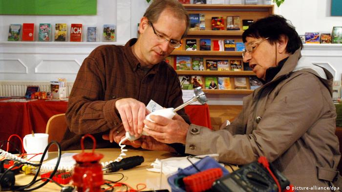 Two people in a repair cafe fixing a food mixing wand