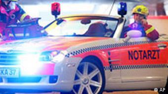 Zwei als Notarzt und Rettungssanitaeter bekleidete Maenner posieren am Dienstag, 15. Nov. 2005, waehrend eines Fototermins zur Messe Medica 2005 in Duesseldorf an einem zum Notarzteinsatzfahrzeug umge