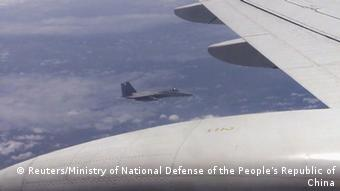 A Japanese F-15 jet (background) and a Chinese Tu-154 jet (foreground) fly over the East China Sea, in this still image from video footage released by China's Ministry of Defense on June 12, 2014.