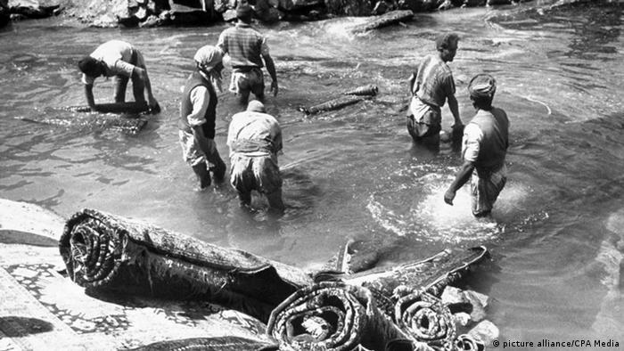 مردان در حال شستن قالی در یک رودخانه. تاریخ عکس نامشخص.