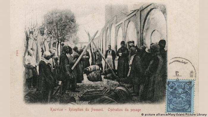 بازار قزوین. مردانی در حال وزن کردن پارچه. تاریخ عکس: ۱۹۰۳ میلادی.